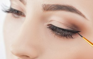 Close up of female eyes. The young woman is applying the eyeliner on her eye